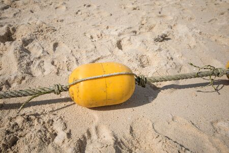 Yellow buoy on the beach.