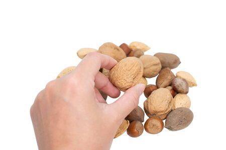 Hand catching walnut with mixed nuts background. Stok Fotoğraf