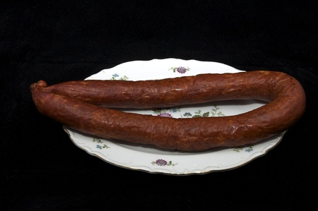 horseflesh: sausage on a plate on a black background