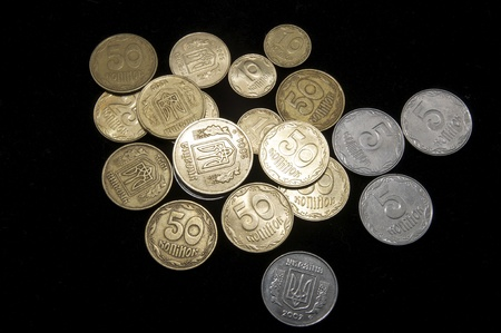 numismatist: scattered small coins of Ukraine on a black background