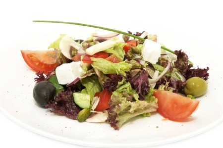 Greek salad with vegetables and cheese on white background