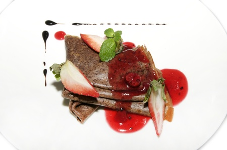 Chocolate pancakes with strawberry jam on a white plate photo