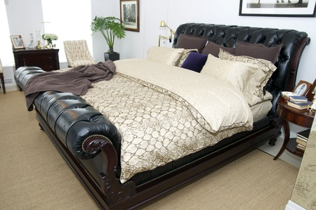bedroom with leather bed and lamps photo