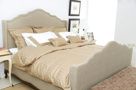a large comfortable bedroom with a bed and lots of pillows Standard-Bild