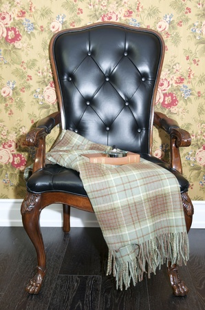 comfortable chair with a blanket and a book to read photo