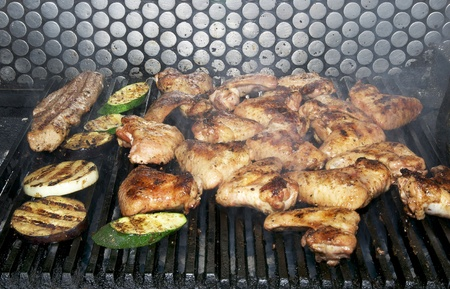 cooking chicken wings in a restaurant on the grill photo