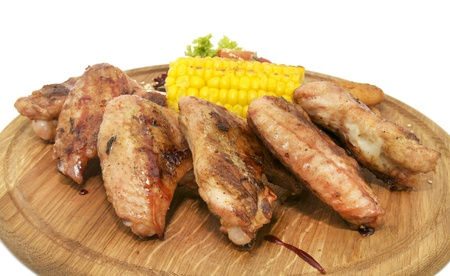 chicken wings with sweet corn on a wooden plate photo