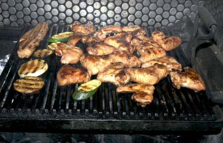 cooking chicken wings on a grill in the restaurant photo