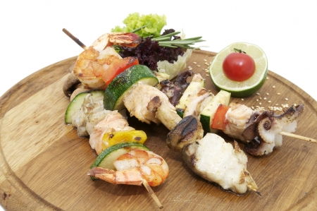 skewers of seafood on a wooden platter in a restaurant photo