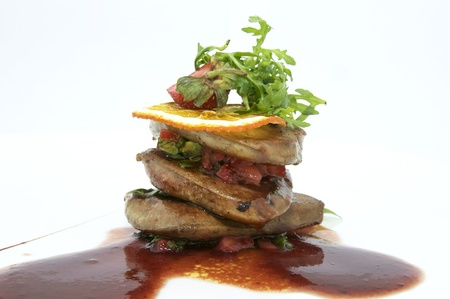 Roast goose liver is decorated with greens and strawberries photo
