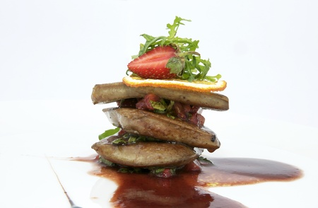 Roast goose liver is decorated with greens and strawberries