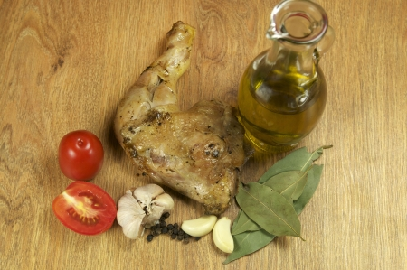 Chicken leg with pepper and butter on a wooden table photo