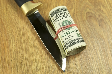 dollars and knife on wooden table photo