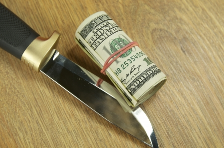 dollars and knife on wooden table Stock Photo - 14746903