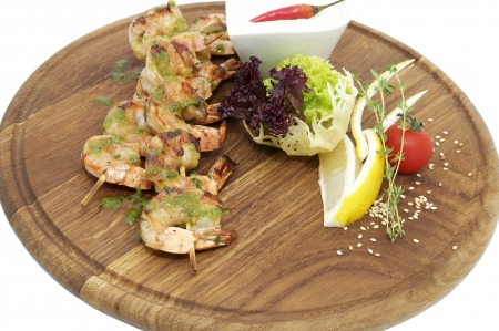 grilled shrimp with a salad on a wooden plate photo