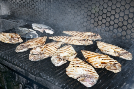 cooking fish on the grill in the restaurant photo