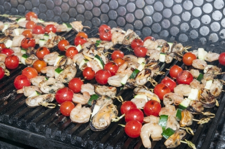 cooking skewers of seafood in a restaurant photo