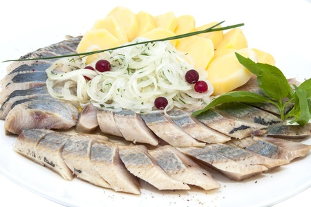 herring and potatoes on a white plate photo