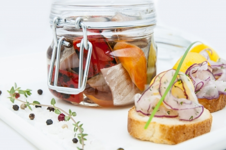 pickled herring in a glass jar with potato canapes Stock Photo - 16343884