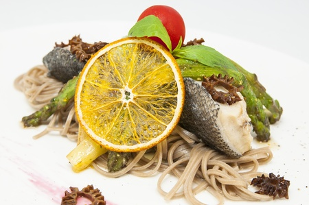 baked fish with spaghetti and mushrooms and vegetables photo