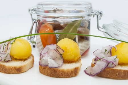 herring in a glass jar with potato canapes Stock Photo - 16448486