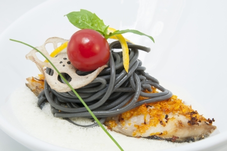 baked fish with black and white spaghetti sauce photo