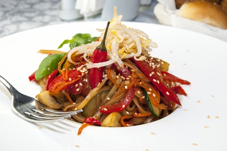 Rice spaghetti with vegetables on a white plate in a restaurant photo