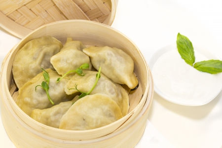 dumplings with sour cream in a wooden bowl photo