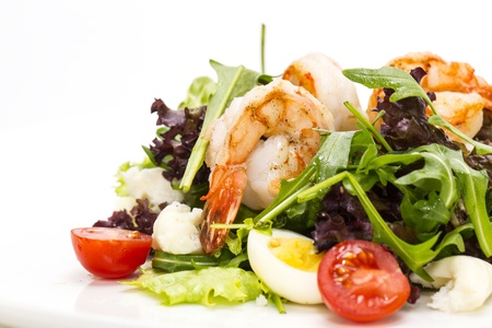 ensaladas verdes y gambas sobre un fondo blanco en el restaurante