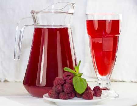 jar of berry drink on the wooden table photo