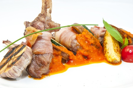 roasted veal ribs with vegetables on a white plate in a restaurant Stock Photo