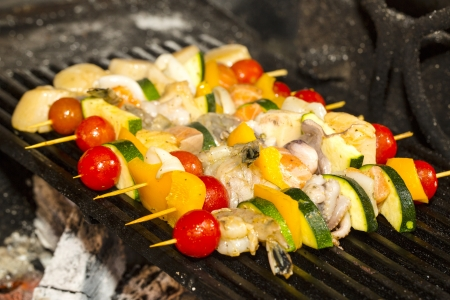 hot grill: skewers of seafood grilling Stock Photo
