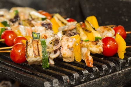skewers of seafood grilling Stock Photo