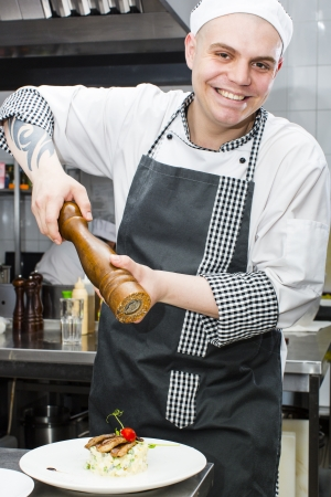 male age 40's: chef preparing food in the kitchen at the restaurant