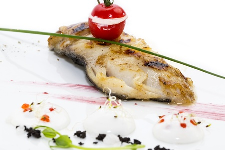 Roasted fillet of grilled fish in a white sauce photo
