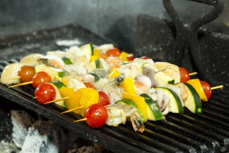 skewers of seafood grilling photo