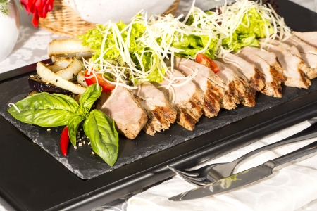 plate of meat and grilled vegetables on a white background photo