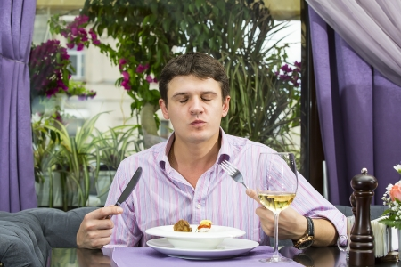 one young man having dinner in a restaurant photo