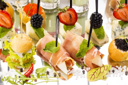 canape with meat seafood and vegetables on a white  photo