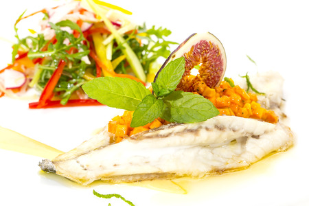 Baked fish with salad on a white in restaurant