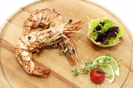 Grilled Shrimp with Orange on a wooden plate photo