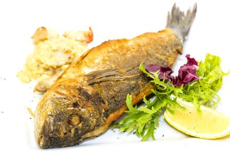 Fried fish dorado with vegetables and lemon photo