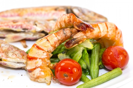 grilled fish with shrimp salad on a white background in the restaurant photo