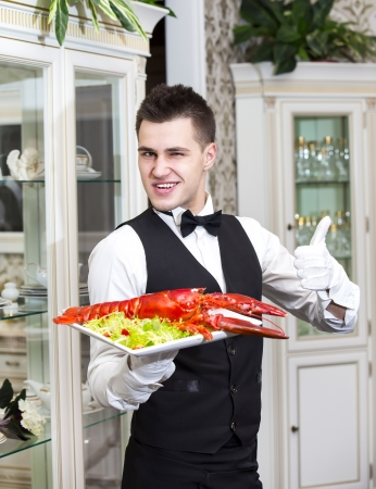 waiter with lobster on a plate in a restaurant photo