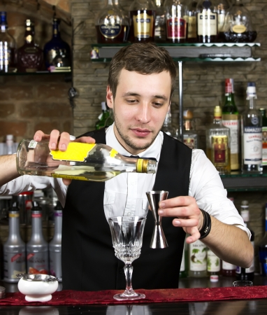 young man working as a bartender in a nightclub bar photo