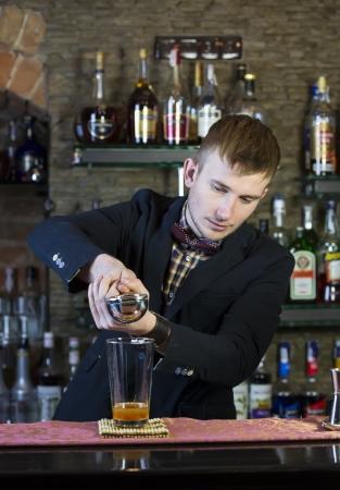 nightclub bar: young man working as a bartender in a nightclub bar Editorial