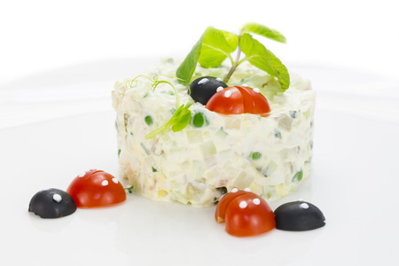 Olivier salad decorated with tomato in the shape of ladybugs