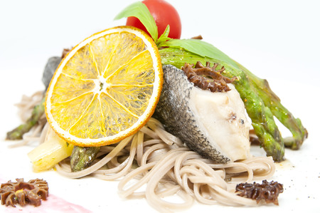 baked fish with spaghetti and vegetables on a white background in the restaurant photo