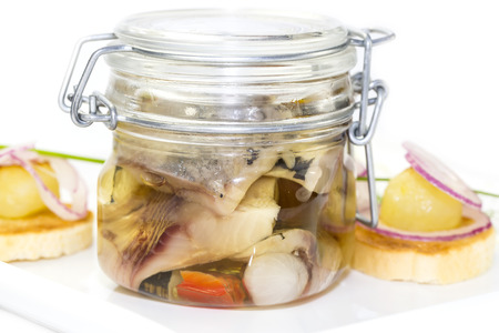 preserving: pickled herring in a glass jar with potato canapes