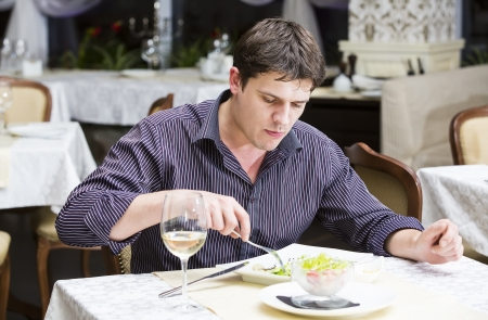dinner wear: young man eating in a restaurant